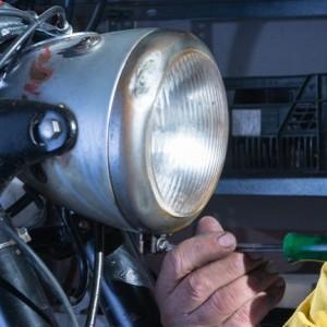 mechanic unscrewing the motorcycle headlight-56935748_Full.e796de60